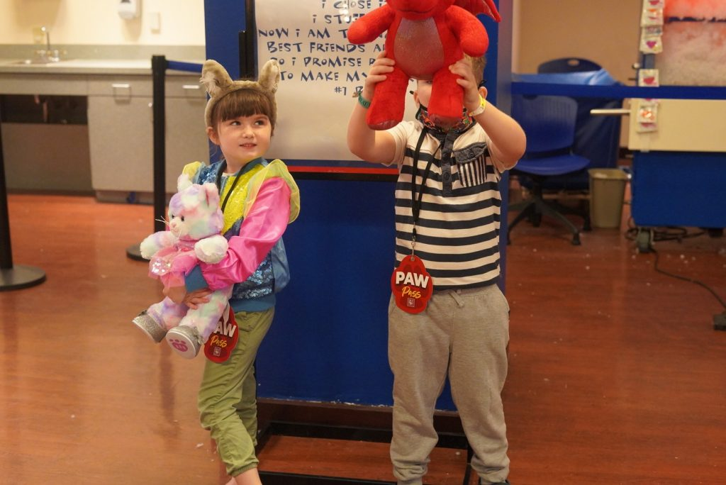 """Two kids in Build-a-Bear showing off their bears.