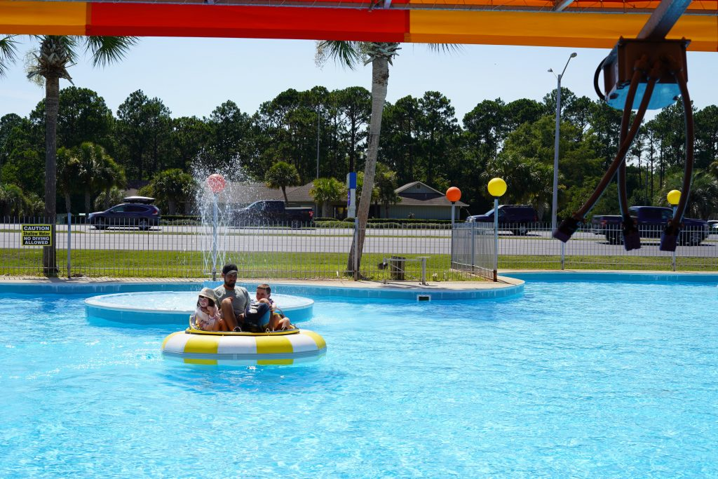A dad with his two kids on a bumper boat in the pool.   Guide to Gulf Shores & Orange Beach Alabama