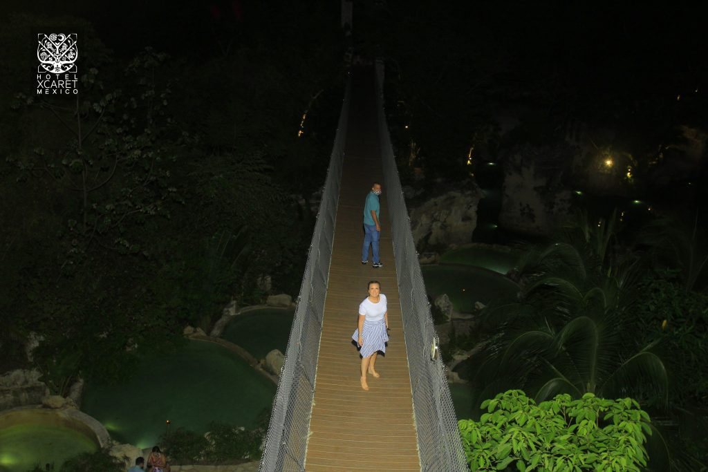 Woman standing the bridge at night.   Guide to Hotel Xcaret in Mexico