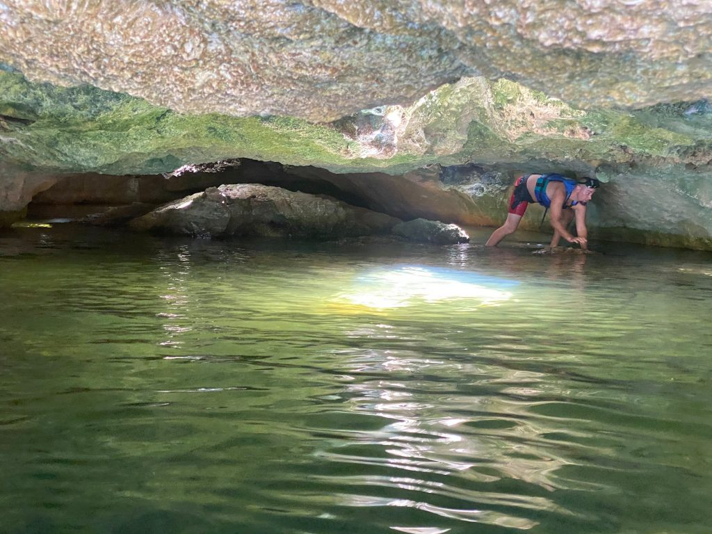Man climbing through caves in the water. | All About XeI-Ha Park in Riviera Maya
