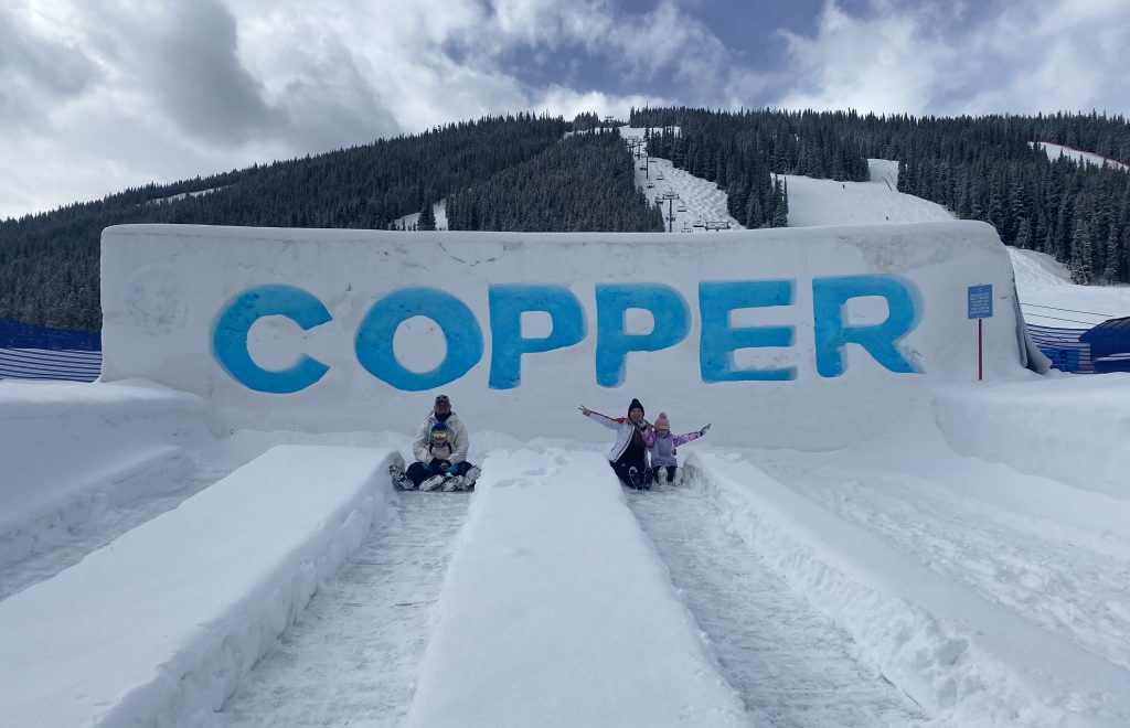 Family posing in front of the Copper Mountain sign, sitting in the tubing lanes and smiling.| Guide to Copper Mountain Resort in Colorado