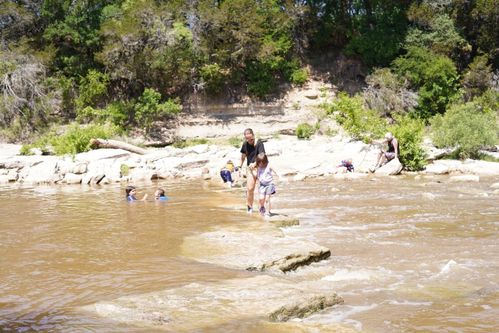 People crossing large rocks in the creek bed.   Dinosaur Valley State Park in Texas