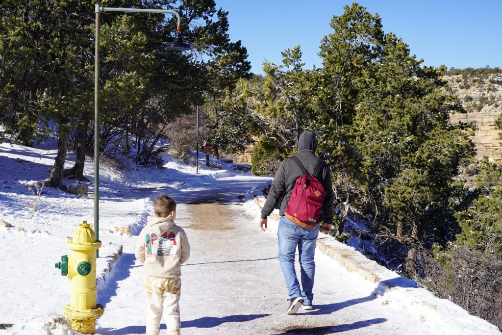 Man and child walking down a snowy path in the Grand Canyon. | Visiting Grand Canyon in the Winter?