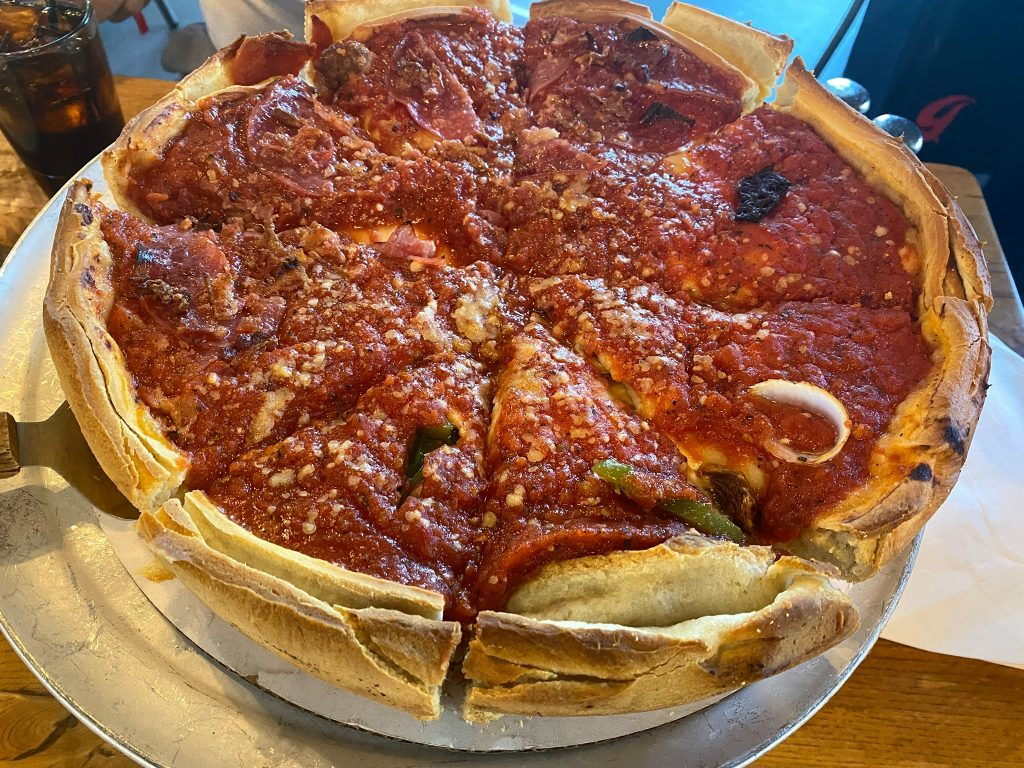 Deep dish pizza on a tray on a table.  Where to eat in Las Vegas