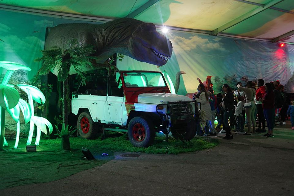 Dinosaur tent area with displays and a jeep for photo opportunities. | Magical Winter Lights Houston