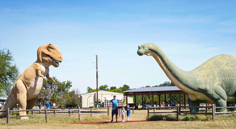 People standing with the large dinosaur statues at the front of the park.   Dinosaur Valley State Park in Texas