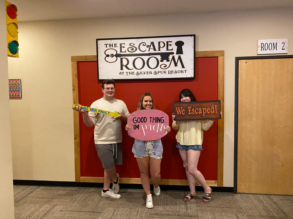 Three people posing with signs in front of Escape Room logo. | Glamping at Silver Spur Resort in Canton, Texas