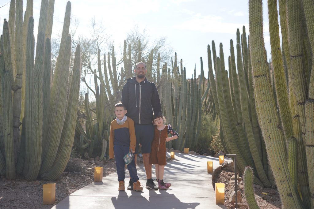 Father with his two kids smiling at the camera standing in the path amongst tall cacti. | Desert Botanical Gardens in Arizona