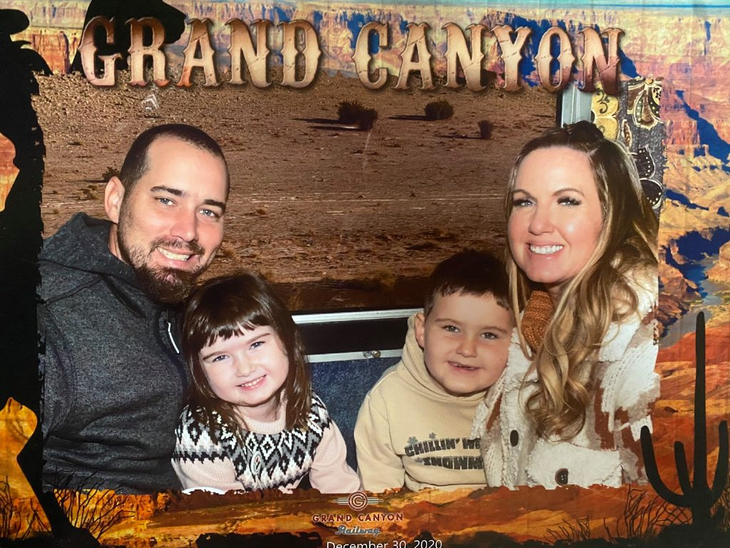 Man, woman and two kids smiling for a picture on the train. | Grand Canyon Railway in Arizona