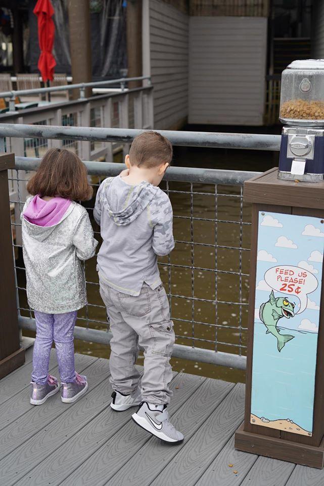 Two little kids feeding the fish at Kemah Boardwalk. | Kemah Boardwalk in Texas