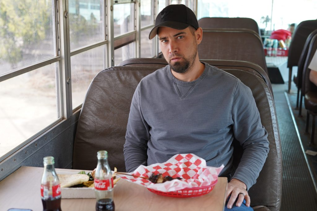 Man sitting inside a school bus eating his Food Shark Truck food in Marfa. | Marfa, Texas- Where to Stay, What to do, & What to Eat