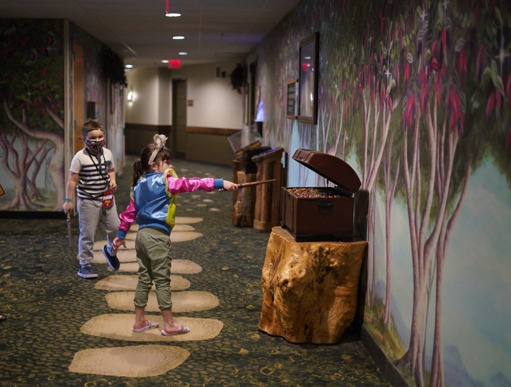 """Two kids in a hallway playing a wand game with treasure chests opening.