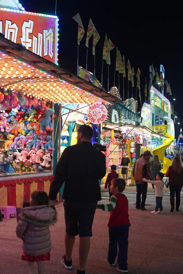 Man walking with his kids at the game area at the Winter Lights. | Magical Winter Lights Houston
