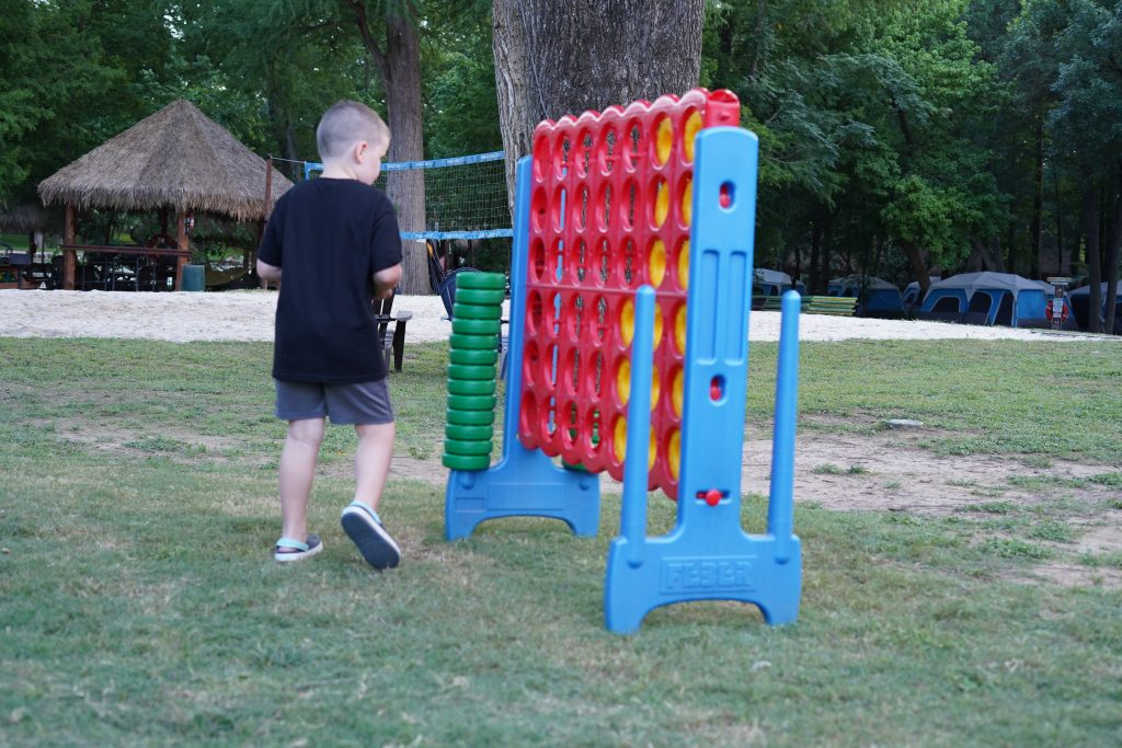 Little boy playing yard games at Son's Island.| Son's Island in Seguin, Texas
