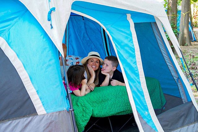 Mom with two kids laying in a tent at Son's Island.| Son's Island in Seguin, Texas
