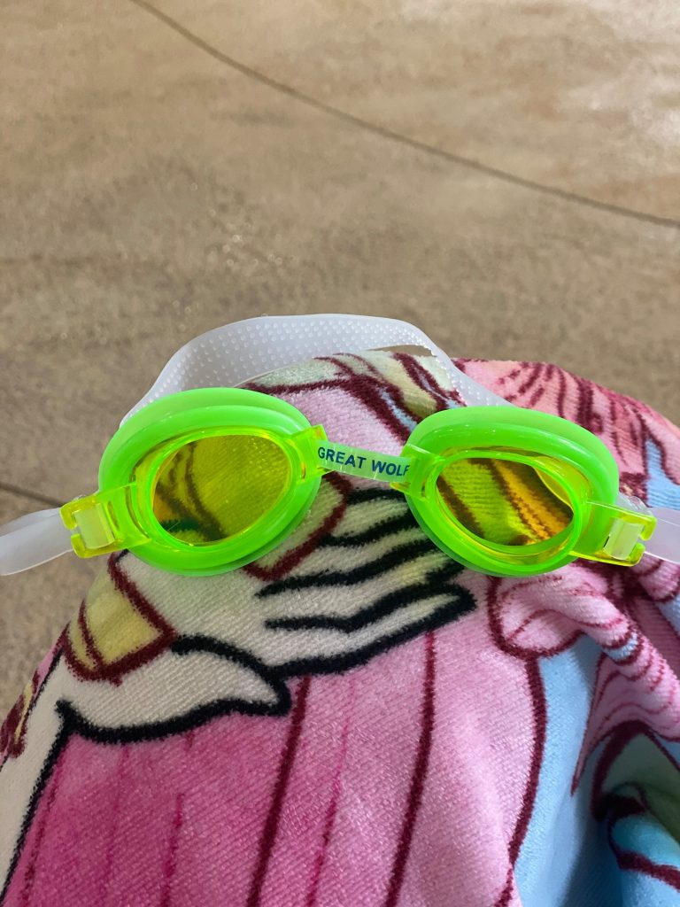 """Green Great Wolf pool goggles on a towel in the pool area.
