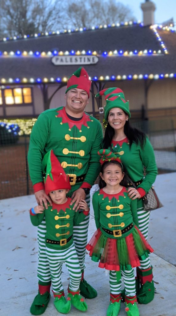 A woman, man, and two little kids dressed in matching elf pajamas outside in the snow. | The Polar Express Train Ride in Palestine, Texas