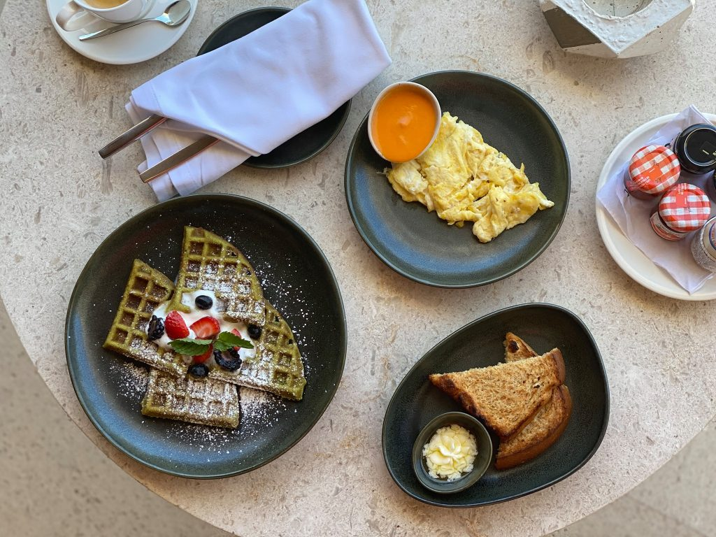 Breakfast food spread on a table including green tea waffles. | A Guide to Nobu Hotel Los Cabos - A Relaxing Girls Trip