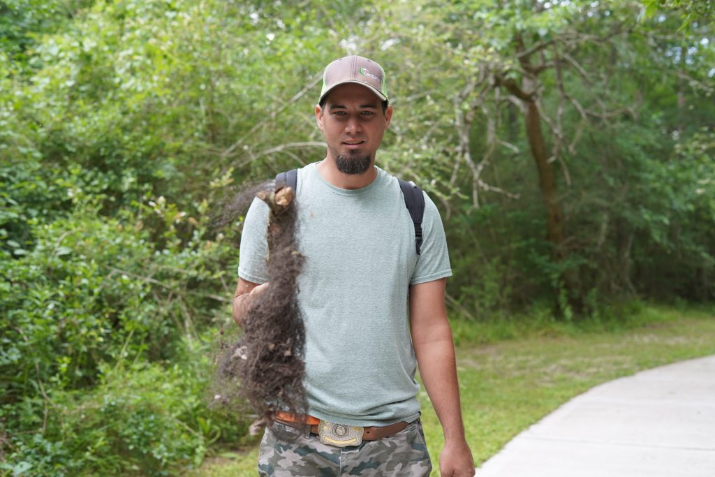Man holding a hairy stick on a path at the nature park in League City. | 6 Things for Families to do at a Nature and Wildlife Park