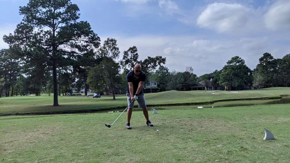 Man teed up to hit his shot on the golf course. | Margaritaville Lake Resort, Lake Conroe