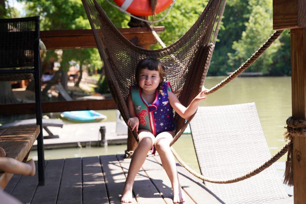 Little girl sitting in a hammock at Son's Island.| Son's Island in Seguin, Texas