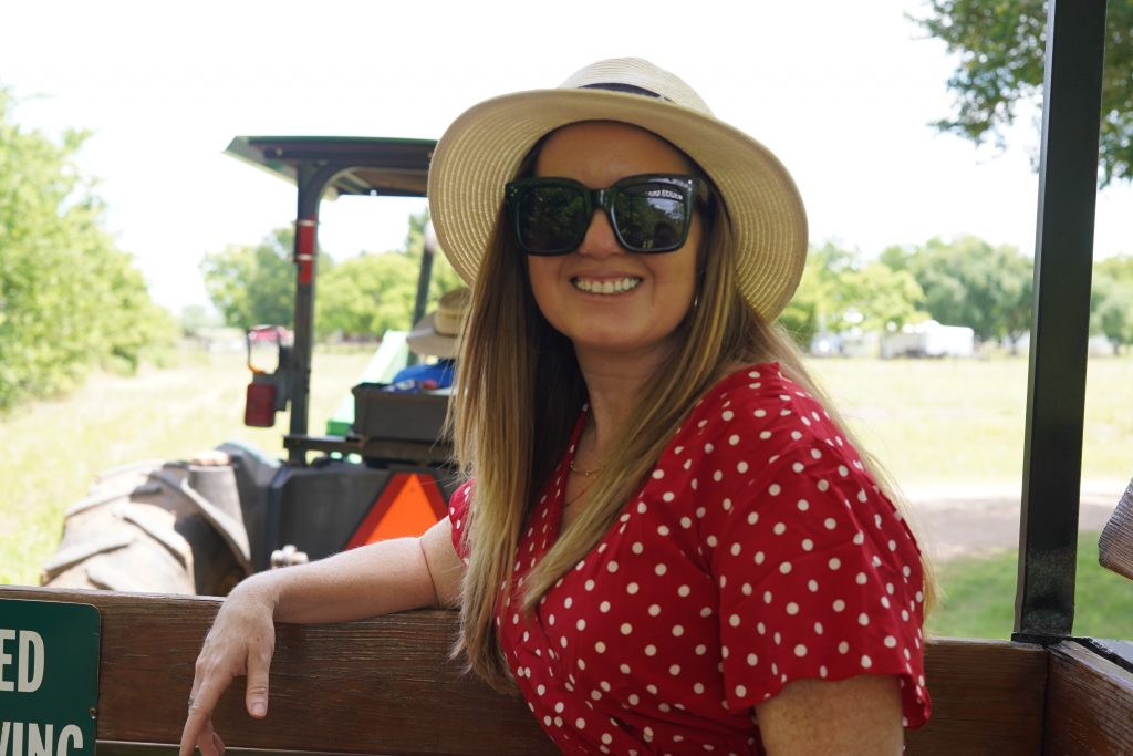 Woman smiling on the hay ride at Blessington Fields. | Blessington Farms in Simonton, Texas