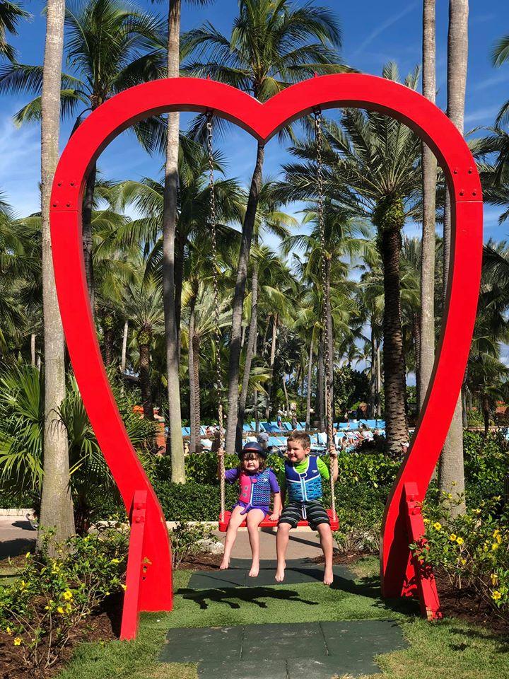 Large heart statue with kids posing on the swing.   Atlantis, Bahamas