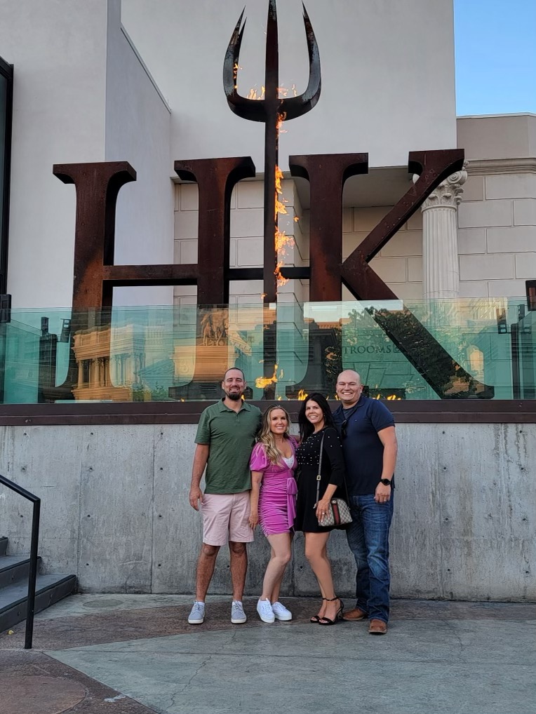 Two couples posing in front of the Hell's Kitchen logo of the restaurant.    Where to eat in Las Vegas
