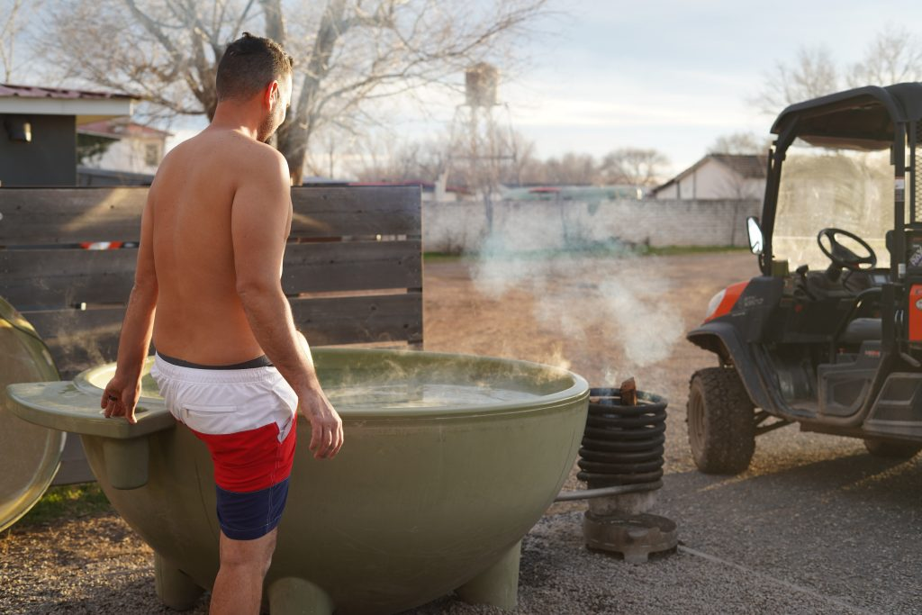 Man stepping into hot tub at El Cosmico in Marfa. | Marfa, Texas- Where to Stay, What to do, & What to Eat