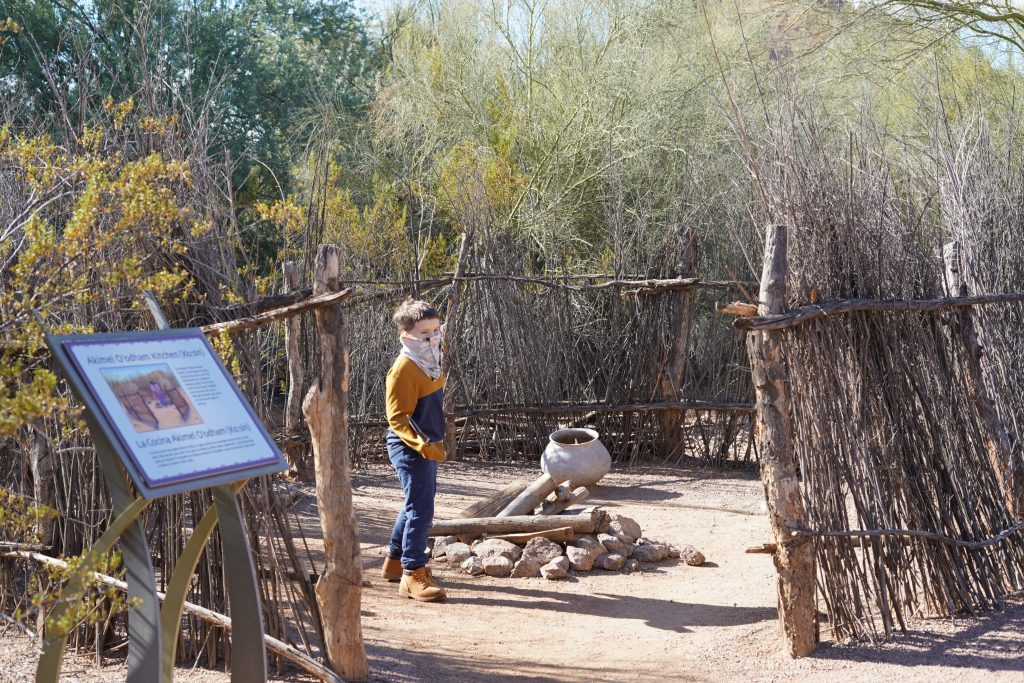 Little boy playing in the Indian camp area and making a pretend fire. | Desert Botanical Gardens in Arizona