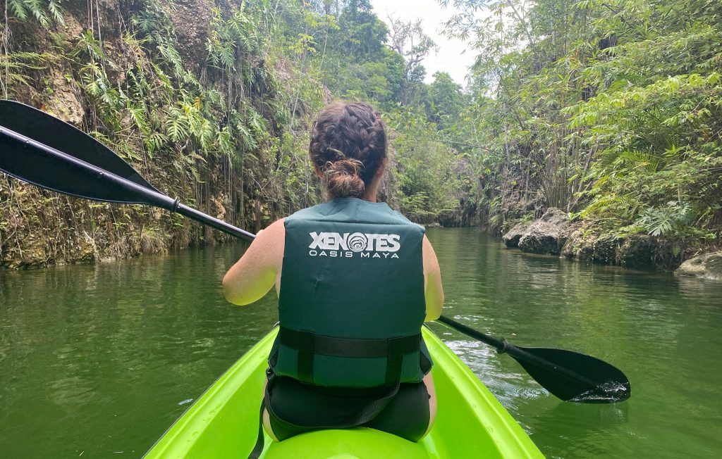A woman kayaking wearing a lifevest that says Xenotes Oasis Maya.  A Guide to Xenotes Water Tours by Xcaret