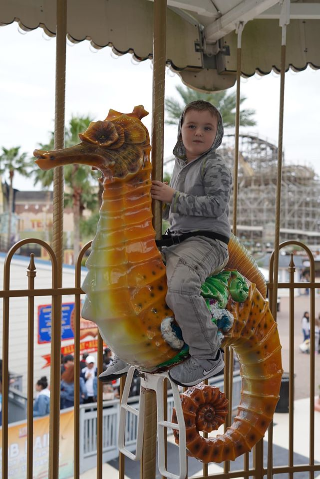 Little boy riding a seahorse on the merry-go-round at Kemah Boardwalk. | Kemah Boardwalk in Texas