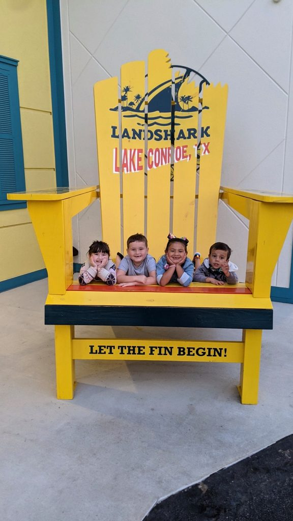 Two girls and two boys sitting on a large yellow chair posing with the Lake Conroe, TX sign. | Margaritaville Lake Resort, Lake Conroe