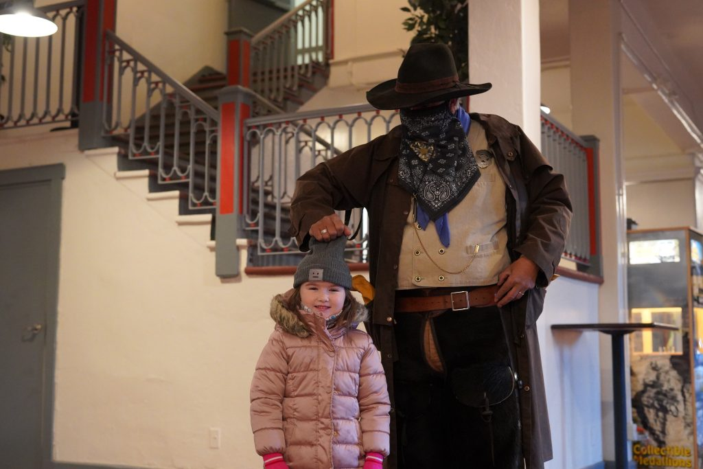 Man dressed as a sheriff pretending to pull off a child's hot. | Grand Canyon Railway in Arizona