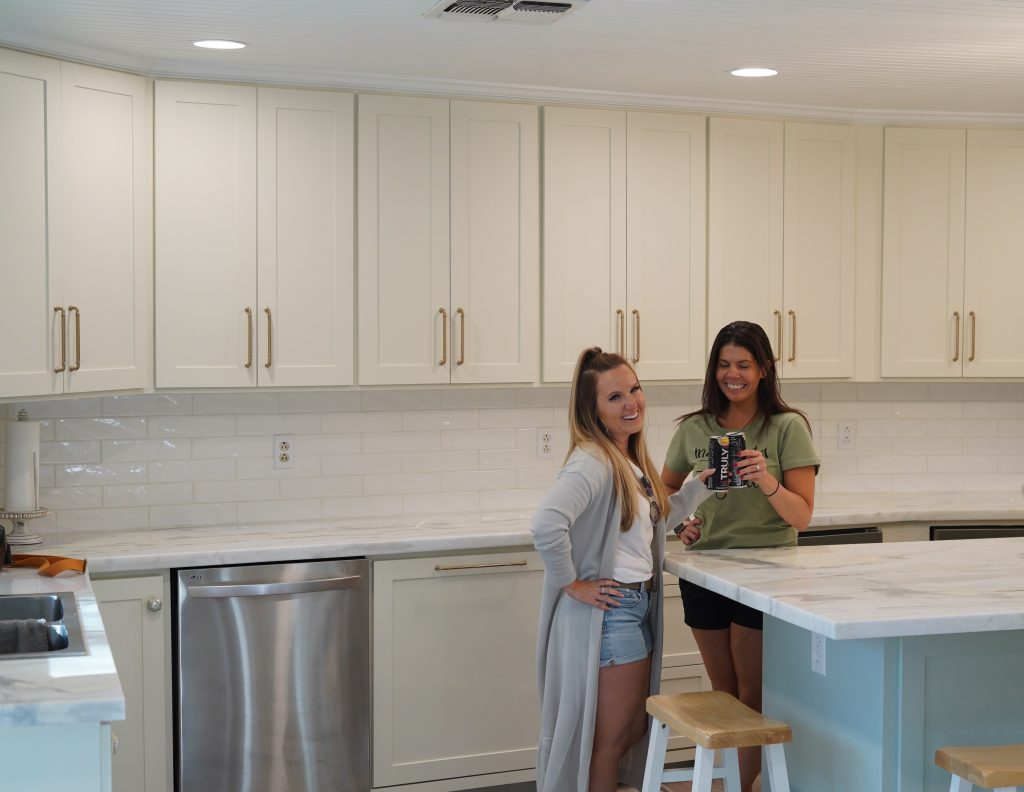 Two women friends toast drinks in the kitchen.| Adult Summer Vacation on Lake LBJ