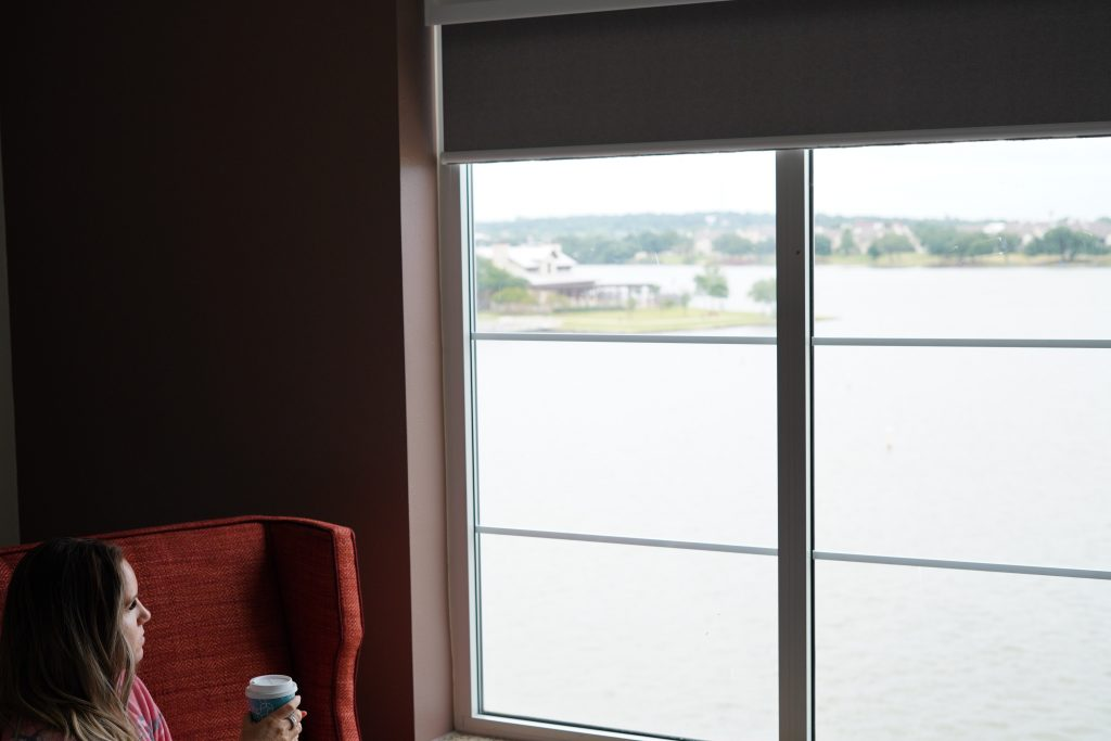 Woman sitting with coffee looking at the outside lake view of the Hilton Garden Inn at the charming Historic Granbury Square.  A Guide to Granbury, Texas