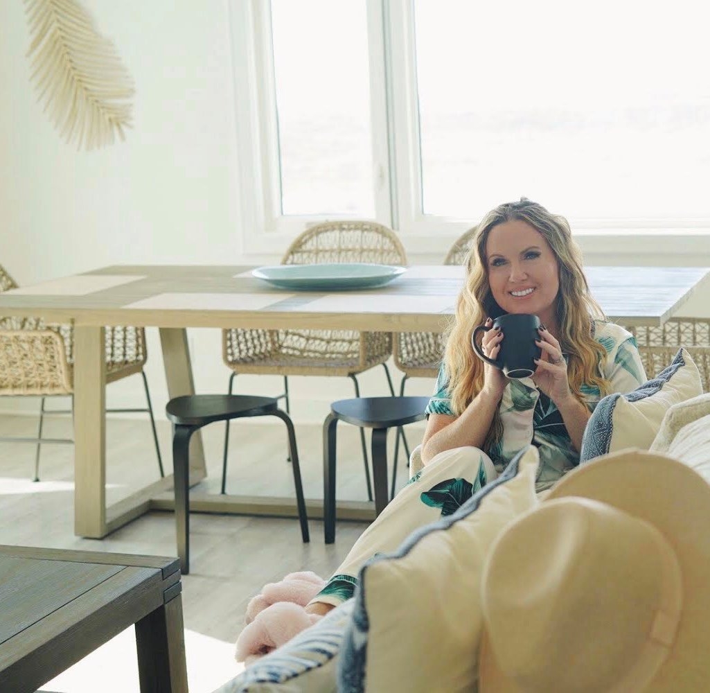 Woman in a living room sitting on a couch drinking coffee and smiling at the camera.| Lively Beach in Corpus Christi, Texas
