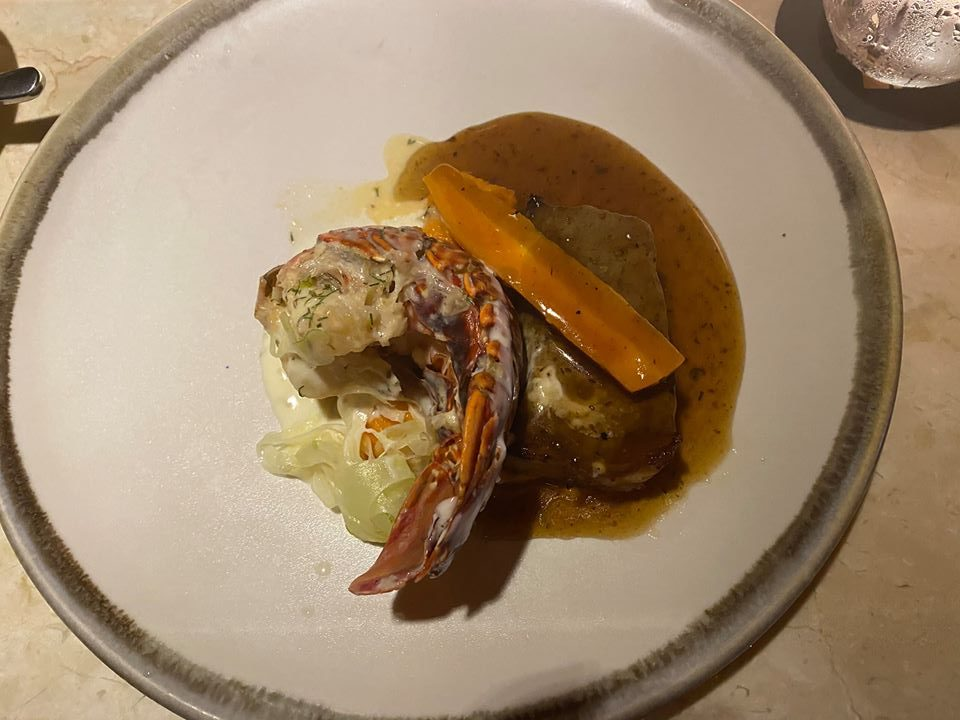 Plate of a lobster and steak dinner.   Guide to Hotel Xcaret in Mexico