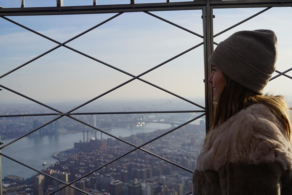 Woman posing while looking at the view from the Empire State Building.   New York City