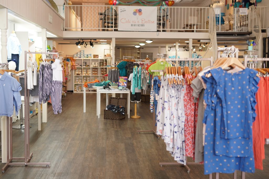 Inside the Madeline Woods Boutique with clothing racks throughout.   A Guide to Granbury, Texas