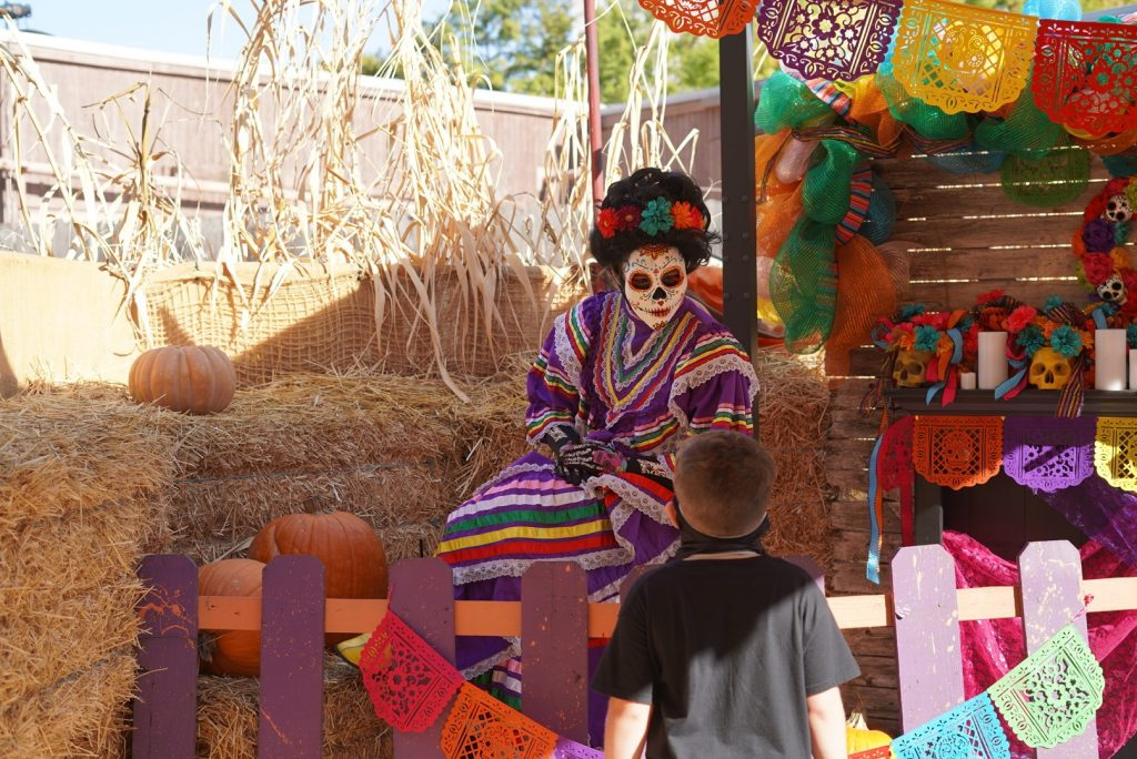 Little boy walking through the trick or treat trail maze talking to one of the spooky characters.   Guide to Six Flags over Texas Hallowfest