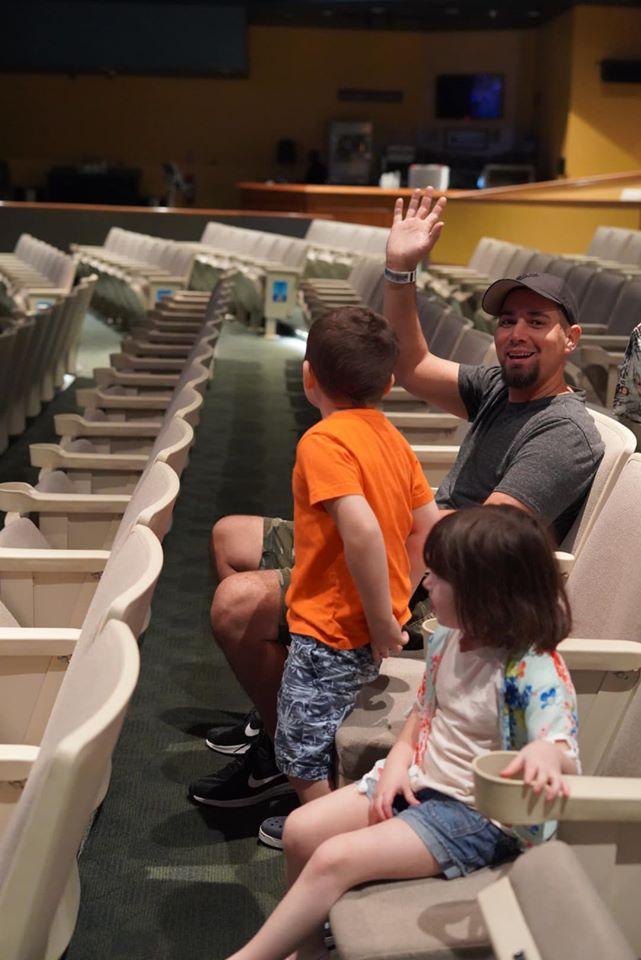 Man witting with his kids at the movie theater at the Atlantis resort.   Atlantis, Bahamas