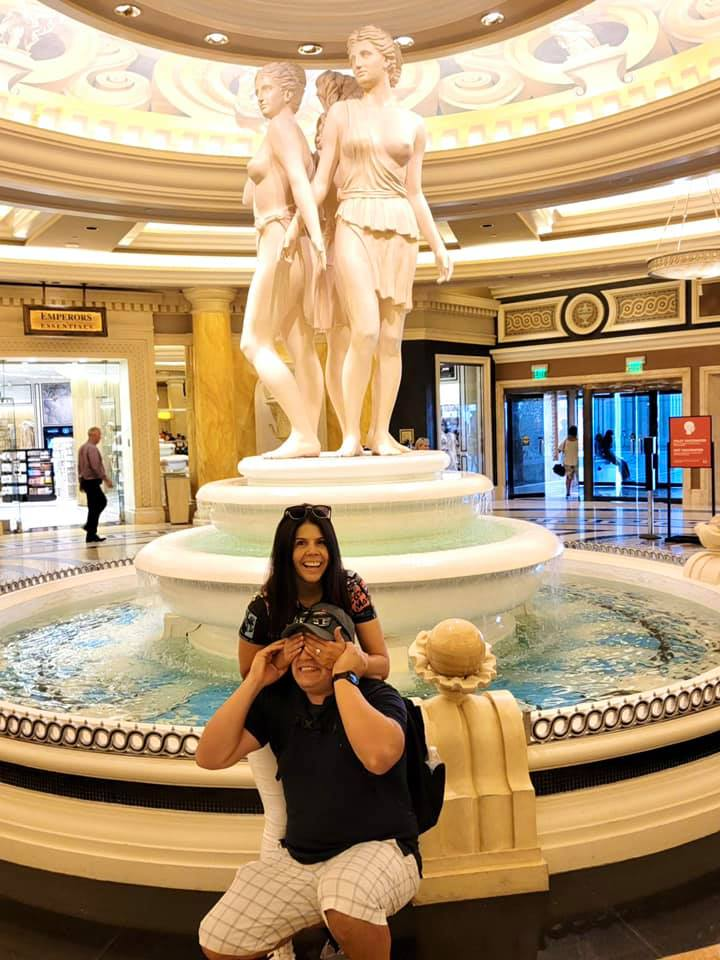 Man and woman posing in front of nude ladies statue inside hotel.   Non-Gamblers Guide to Las Vegas