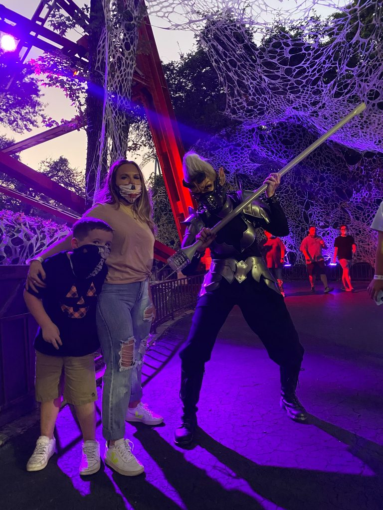 Woman and little boy posing with a spooky character at night at Six Flags.   Guide to Six Flags over Texas Hallowfest