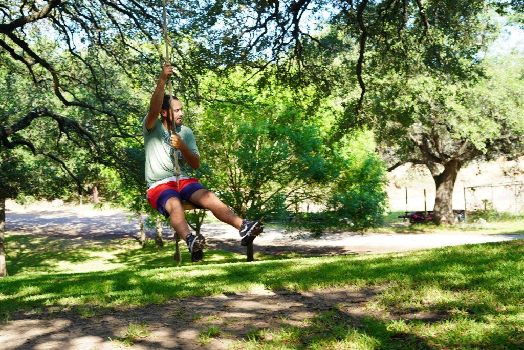Man swinging on tree swing outside.| Adult Summer Vacation on Lake LBJ