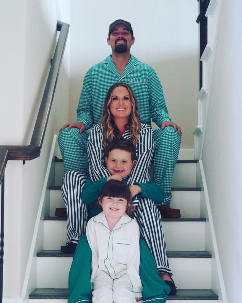 A woman, man, and two little kids dressed in matching green pajamas posing on a staircase. | The Polar Express Train Ride in Palestine, Texas
