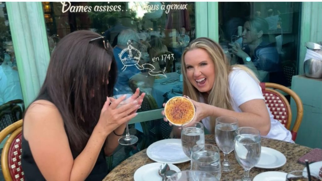 Two women sitting at a table outside of restaurant laughing and eating and drinking.  Where to eat in Las Vegas