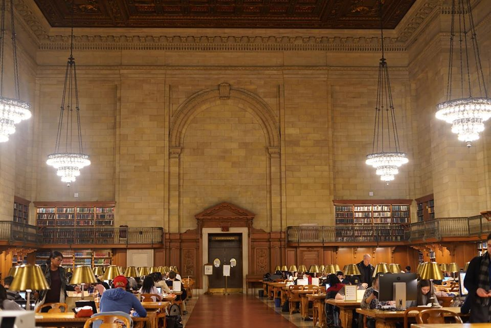 People studying inside the New York Public Library.   New York City