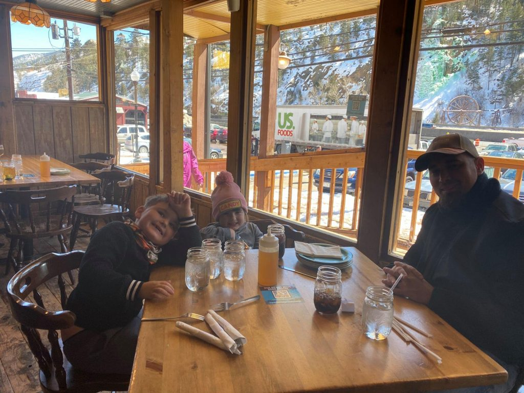 Man and kids sitting at table in restaurant in Colordao.| Best Places to Visit in Colorado
