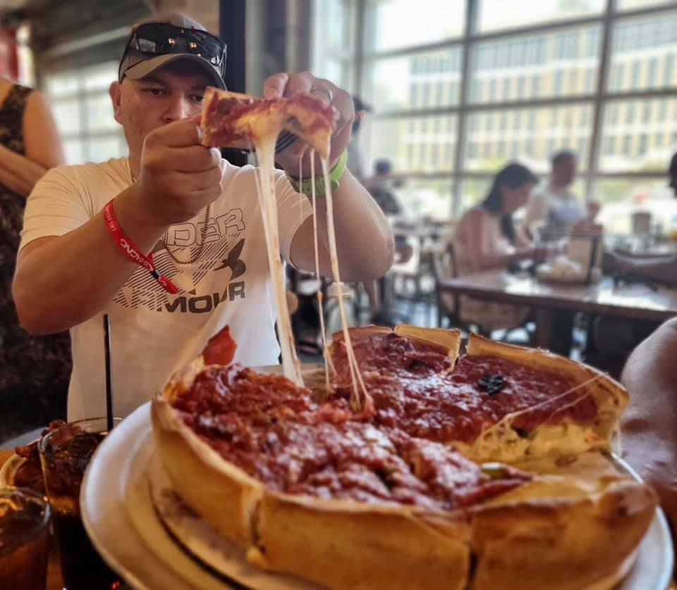 Deep dish pizza with a man pulling a piece to his plate with a strings of cheese dripping.  Where to eat in Las Vegas